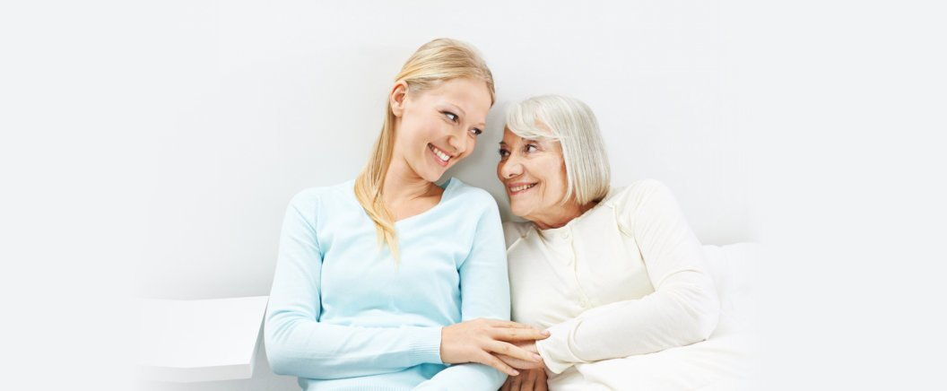 Young woman and old senior woman smiling each other
