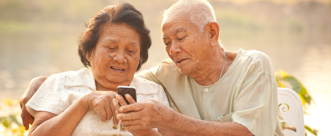 elders holding mobile phone