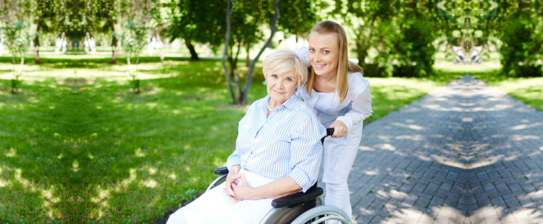 caregiver assisting old woman