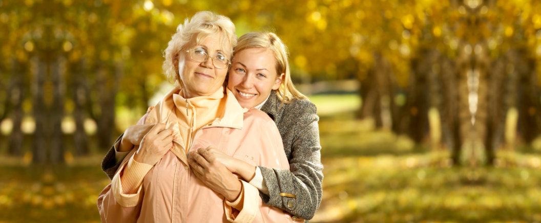 caregiver hugging old woman